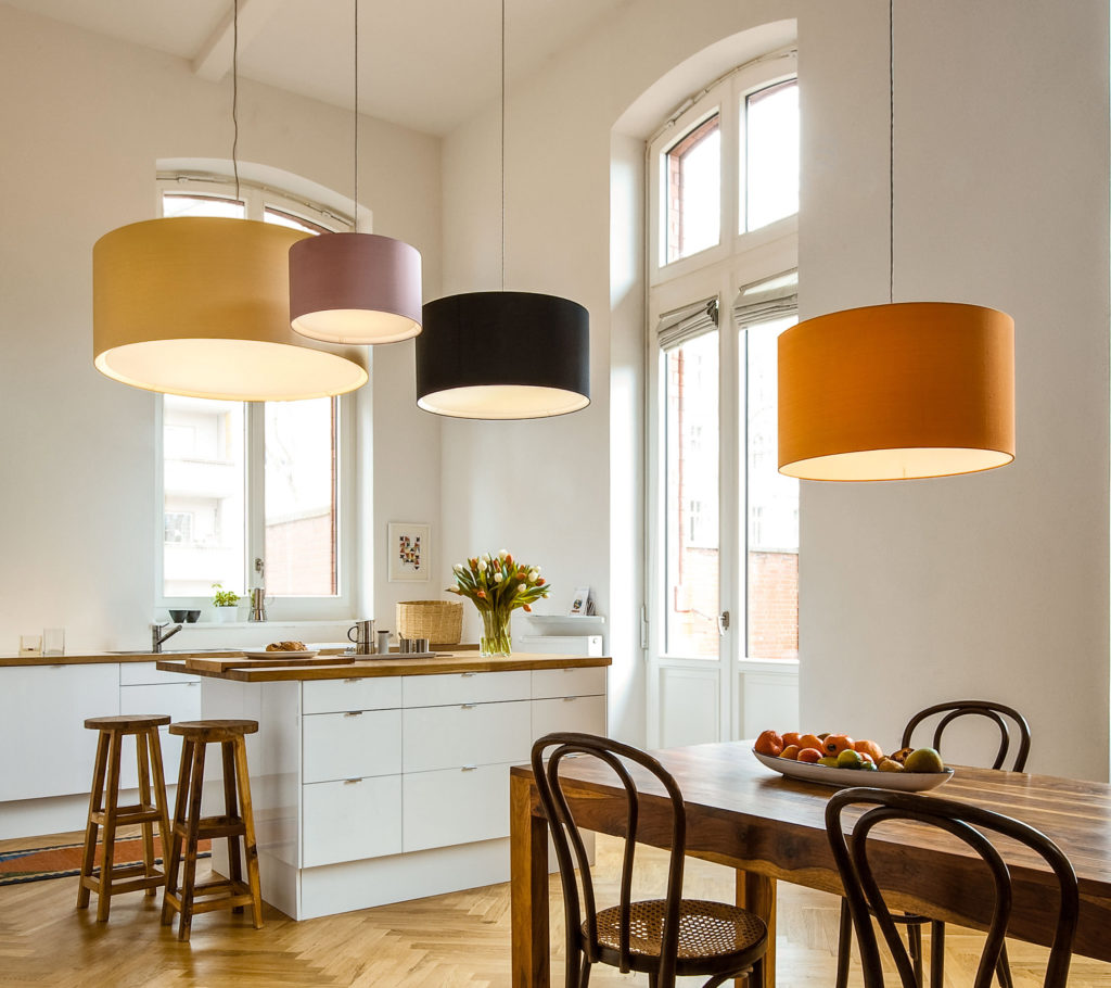 Cylindrical pendant lamps CYLS drum by filumen hang above a white kitchen island. The colorful round fabric shades contrast the wooden designer interior.