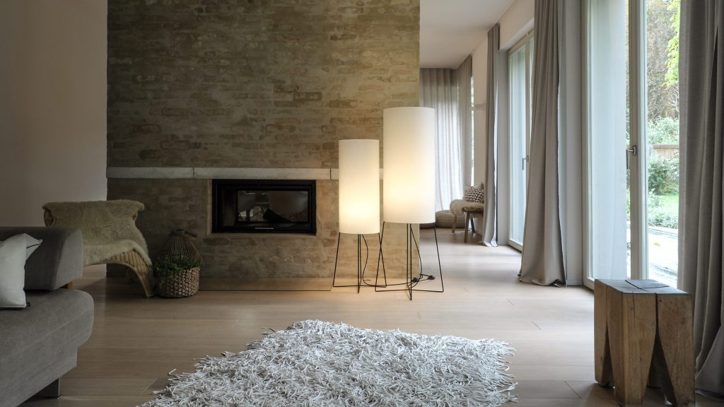 Floor lamp COLUMN standing in two sizes in a quiet, elegantly designed living room. Through the light grey fabric shade on the black cross foot it exudes soft light, creating ambiance.