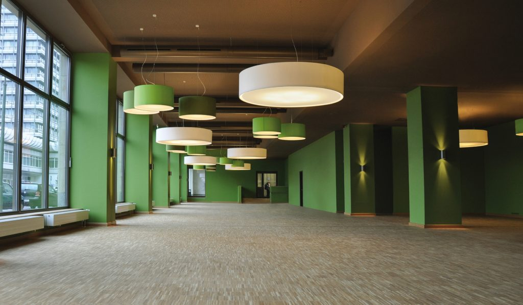 Many large custom filumen CYLS drum pendant lamps hang in a green loft.
