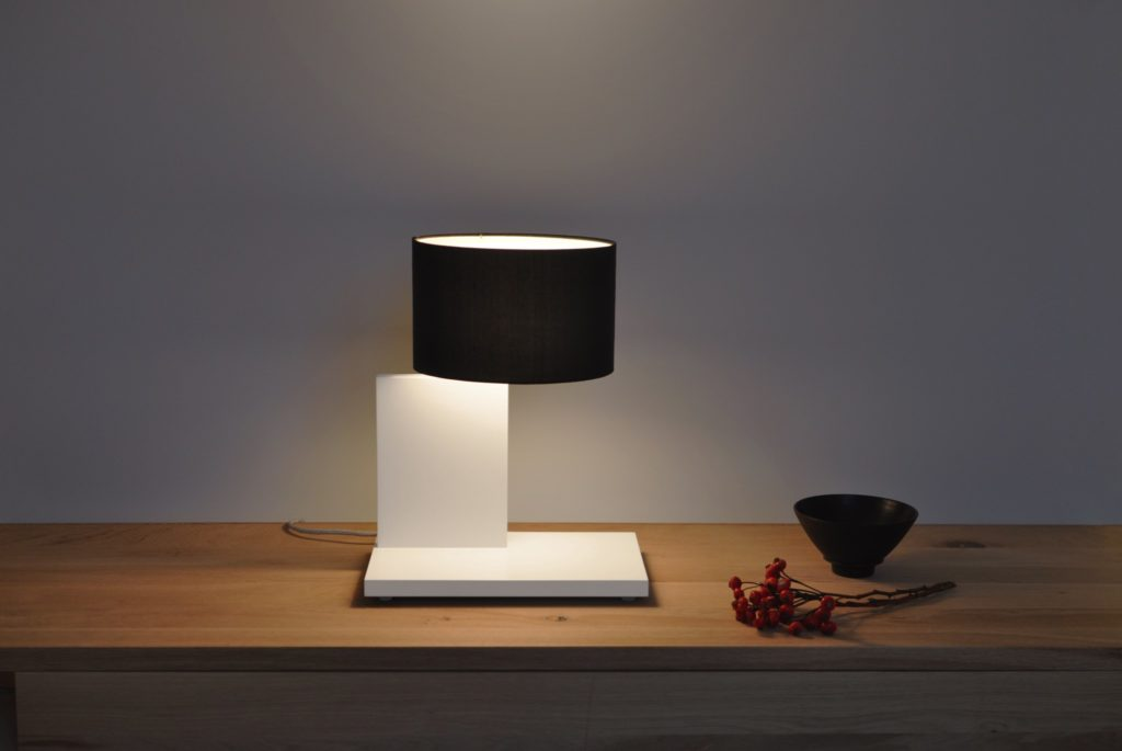 The unconventional table lamp filumen CYLS sight with round black textile shade and white foot reminds of classic Bauhaus design.