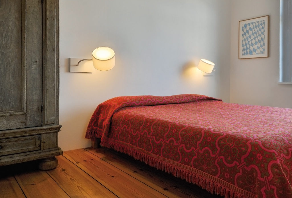 Two all-white wall and reading lamps filumen Cubic Gates Read with flexible arms and textile shades above a bed.