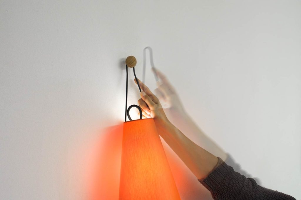 Versatile wall lamp Mia by filumen with orange fabric shade is being attached to the wooden knob by hand.