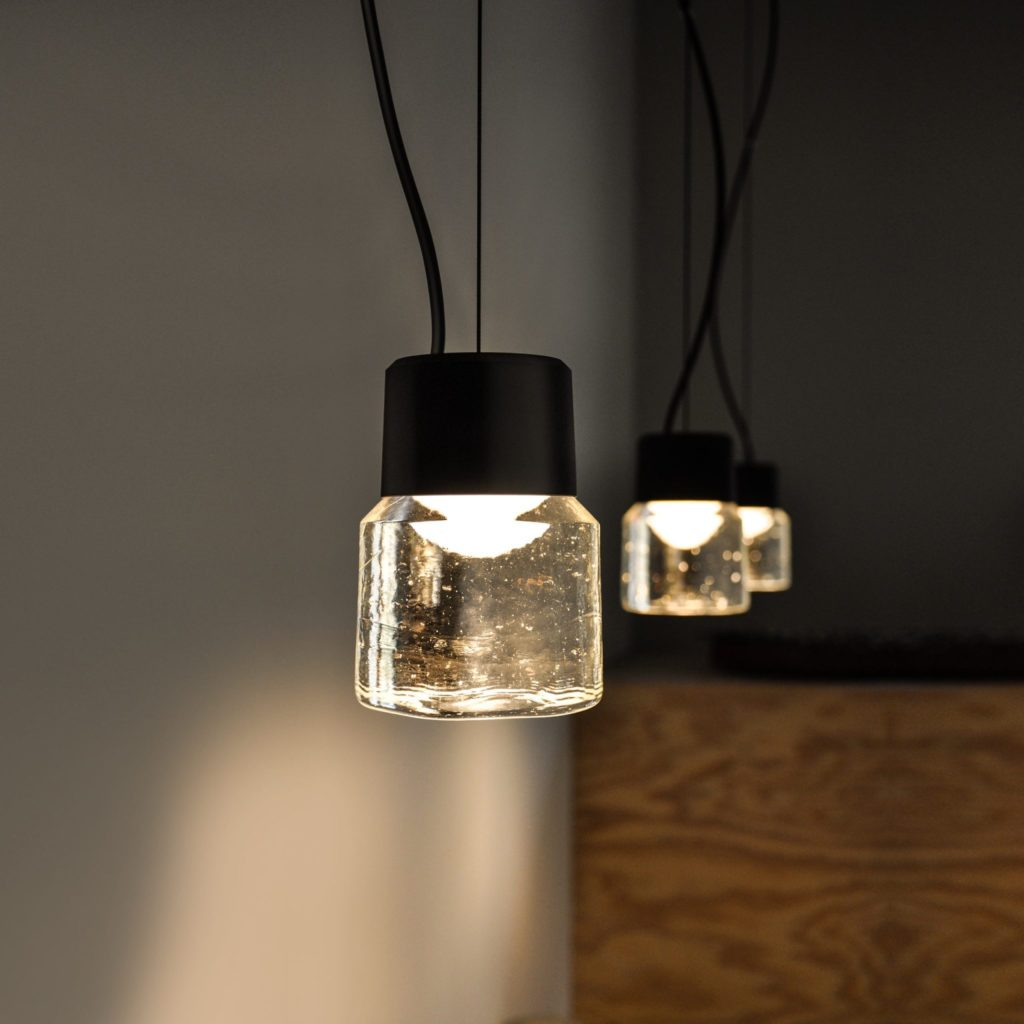 Designed by joung Berlin-based design studio büro famos, the LED pendant lamp CAST charms with its combination of hand-made unique cast glass and clean black anodized aluminium.