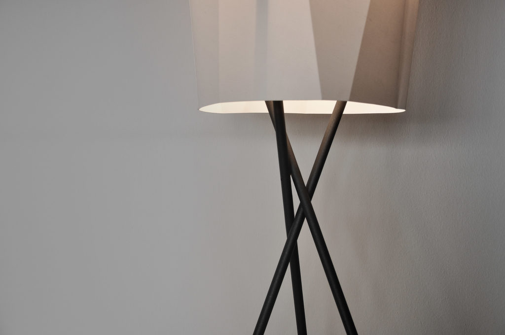 The tripod of the floor lamp BENT Mikado is illuminated by the LED light within the folded textile shade made out of white fabric.