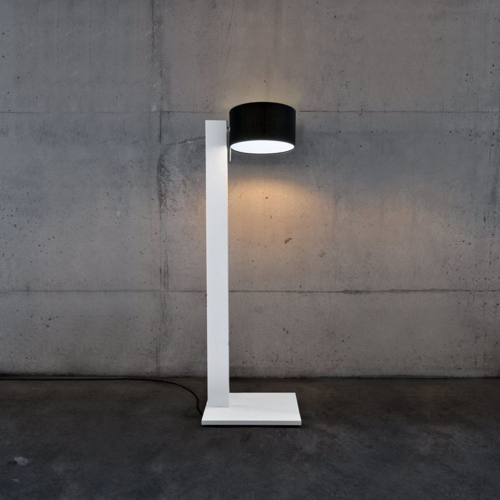 The minimalistic white corpus and clean lines of the floor and reading lamp CYLS butler in front of the exposed concrete forms a stark contrast to the black round fabric shade emitting soft light.
