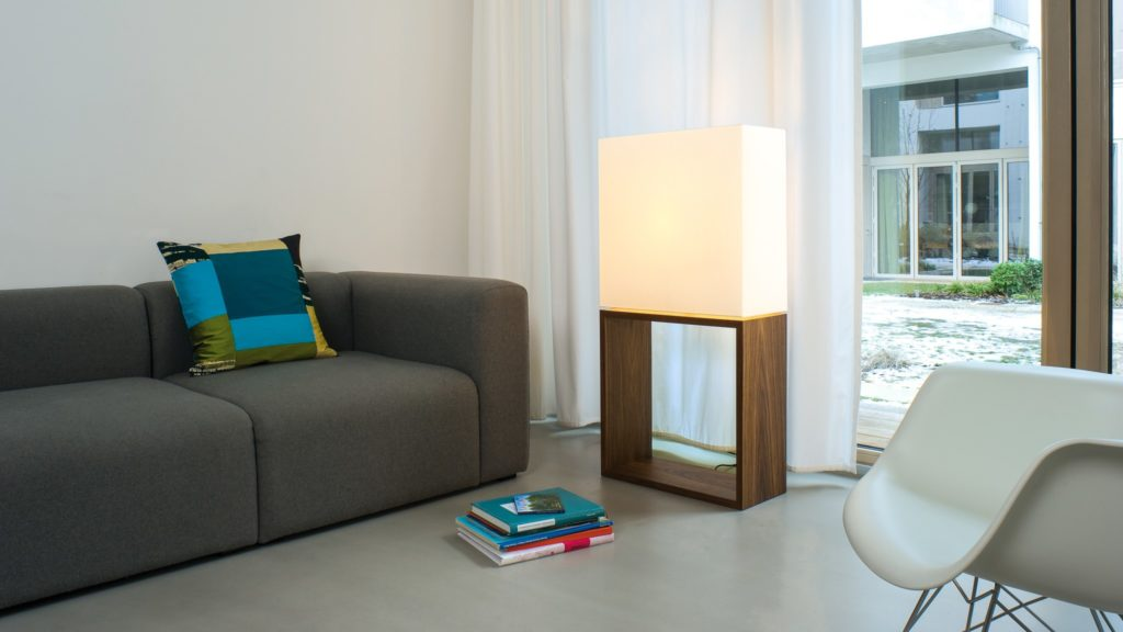 Standard lamp CG Floor illuminates a living room full of design furniture. On the square walnut wood corpus stands a square white textile shade with a LED light inside.