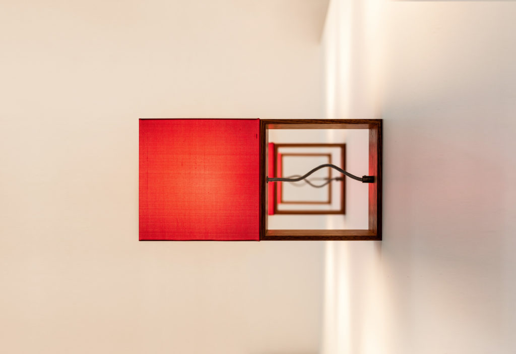 Filumen Cubic Gates Sign wall lamp with red textile shade. The thin wooden frame moves gives it space and causes a signal effect.