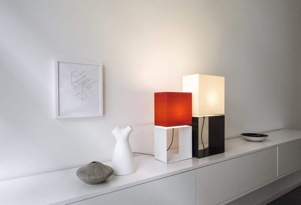 Two table lamps filumen Cubic Gates little und Cubic Gates big with square textile shade and ultra thin metal frame standing on a white sideboard.