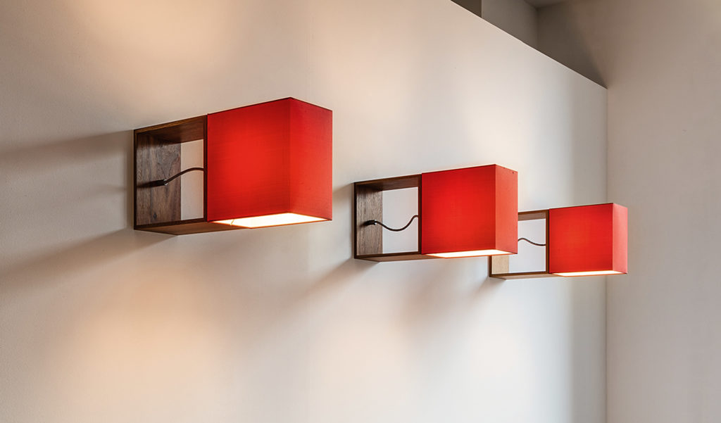 The wall lamp Cubic Gates by filumen with red fabric shade as a series. The square wooden frame sets it apart from the wall.