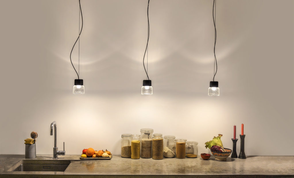 An ensemble of CAST LED pendant lamps illuminates a kitchen counter. The combination of individual cast glass and minimalistic black aluminium obtains the hanging lamp its charme.