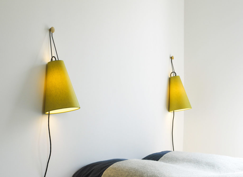 Two conical wall lamps Mia by filumen with yellow green fabric shade, handles suspended from a wooden knob above the bed.